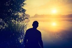 Человек наблюдая восход солнца над озером людской силуэт Стоковые Фото