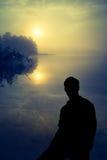 Человек наблюдая восход солнца над озером людской силуэт Стоковое фото RF