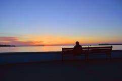 Человек наблюдая заход солнца Стоковые Изображения