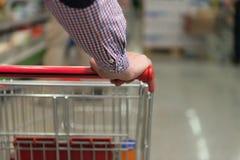 Человек нажимая магазинную тележкау в конце-вверх обувного магазина Стоковая Фотография RF