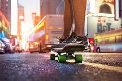 Человек наслаждается катанием на скейтборде на улице города на времени захода солнца Тема концепции спорта людей скейтбордиста Стоковое Фото