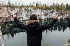 Человек наслаждается красивым видом на озеро от hilltopl и хорошей погодой в Karelia Вокруг утесов Стоковые Изображения
