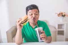 Человек наслаждается съесть гамбургер дома стоковые изображения rf