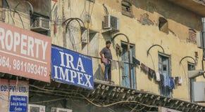 Человек на ветхом балконе Дели Стоковое фото RF