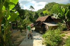 Человек на велосипеде в этнической деревне стоковое фото rf
