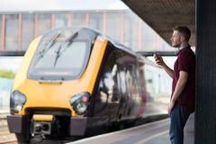 Человек на железнодорожном вокзале используя мобильный телефон на платформе Стоковые Изображения