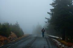 Человек на законцовке дороги в тумане Стоковая Фотография