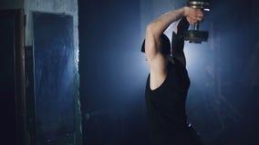 Человек на зеркале поднимает гантель Темный спортзал с голубым backlight видеоматериал
