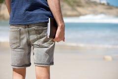 Человек на каникулах держа книгу дневника на пляже Стоковая Фотография RF