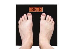 Человек на масштабах с много весом и проблемами здоровья, надписью - помощью Стоковые Фото