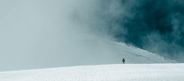 Человек на ноге горного пика в облаках Стоковые Фото