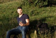Человек на походе в природе используя телефон Стоковые Фотографии RF