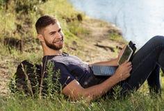 Человек на походе в природе используя цифровую таблетку Стоковые Изображения RF
