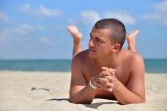 Человек на пляже лежа в песке смотря к стороне Молодой наслаждаться мужчины стоковые изображения rf