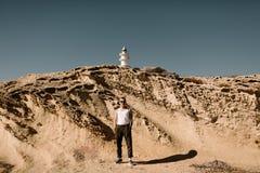 Человек на пляже Человек около песочных скал Человек на заднем плане маяка Маяк Стоковое фото RF