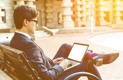 Человек на стенде используя компьтер-книжку Стоковое Фото