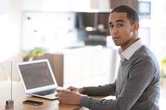 Человек на столе с компьтер-книжкой в офисе Стоковое Изображение