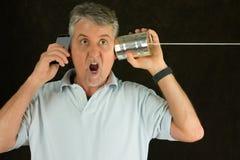 Человек на телефоне жестяной коробки и умном сотрясенном телефоне раздражанными над технологией маркетинга стоковая фотография rf