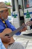 Человек на улице играя гитару стоковое изображение