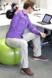 Человек на шарике разрабатывая с kettlebell во время работы offce стоковая фотография