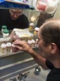 Человек на шкафе медицины Стоковые Изображения RF