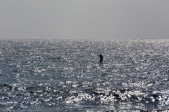 Человек на surfboard на море в Точках доступа серебра захода солнца Стоковое Изображение