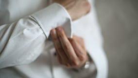 Человек носит белые рубашку и запонки для манжет акции видеоматериалы