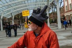 Человек носит шляпу средн-пальца на выходе анти--инаугурации на государственном университете Орегона Стоковая Фотография