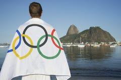 Человек нося олимпийский флаг Рио-де-Жанейро спортсмена Стоковое фото RF