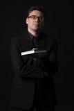 Человек нося черный костюм представляет книгу для того чтобы прочитать Стоковые Изображения RF