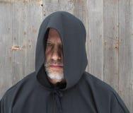 Человек нося черный с капюшоном глаз накидки одного Стоковое Изображение