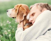 Человек обнимает его любимую собаку стоковые изображения rf