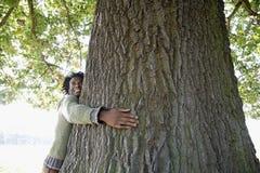 Человек обнимая ствол дерева на парке Стоковые Изображения RF