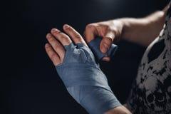 Человек оборачивает руки с голубыми обручами бокса Стоковые Фото
