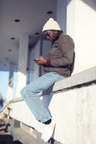 Человек образа жизни стильный молодой африканский используя smartphone в городе стоковые фото