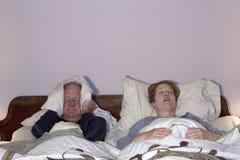 Человек общаясь с храпя женой Стоковые Фото