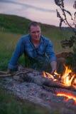 Человек около костра во время захода солнца Стоковая Фотография
