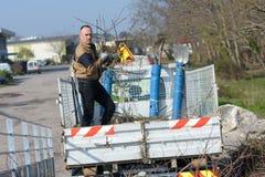 Человек опорожняя сор от трейлера тележки на месте захоронения отходов общины Стоковая Фотография