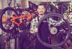 Человек определяет колесо велосипеда Стоковая Фотография