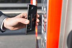 Человек оплачивает его билет перехода с его мобильным телефоном на платформе стоковые изображения