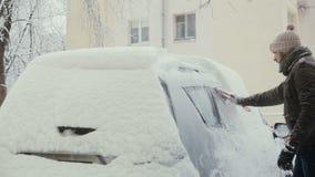 Человек освобождает снег от его автомобиля на улице в зиме, заднем взгляде, видеоматериал