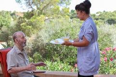 Человек осуществляющий уход давая старшую еду в жилом доме стоковые фотографии rf