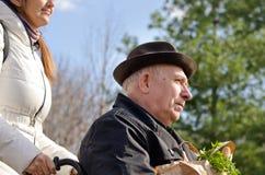 Человек осуществляющий уход принимая пожилое посещение магазина бакалеи человека Стоковая Фотография RF