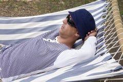 Человек отдыхая в гамаке Стоковое фото RF