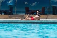 Человек отдыхая на бассейне стоковое фото rf