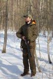 Человек охотника в темной хаки одежде в лесе Стоковые Изображения