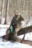 Человек охотника имеет остатки и выпивая чай в лесе Стоковые Фотографии RF