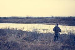 Человек охотника стоя на речном береге в ожидании успешного звероловства Стоковая Фотография