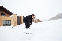 Человек очищает лопаткоулавливатель снега на зиме Стоковое Изображение