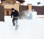 Человек очищает лопаткоулавливатель снега на зиме Стоковые Изображения
